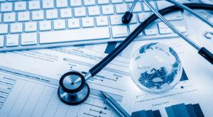 Stethoskop, wie es Ärzte und Pflegekräfte benutzen, neben einer Tastatur und zahlreichen Unterlagen.